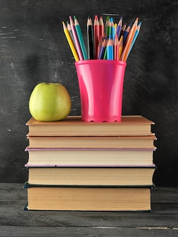 Pila di libri e un bicchiere di cancelleria blu con matite colorate in legno