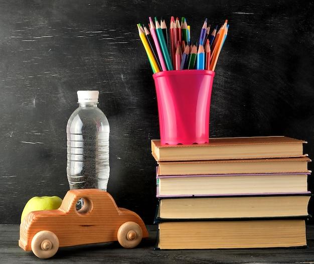 Pila di libri e un bicchiere di cancelleria rosa con matite colorate in legno
