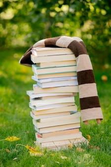 Pila di libri e una sciarpa sull'erba verde in autunno