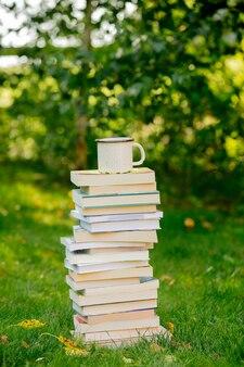 Pila di libri e una tazza di caffè sull'erba verde in autunno