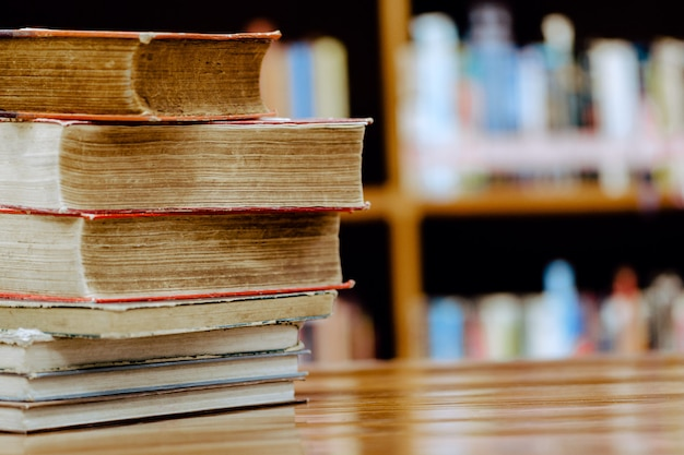 Pila di libri in biblioteca. concetto di istruzione biblioteca con molti scaffali e libri