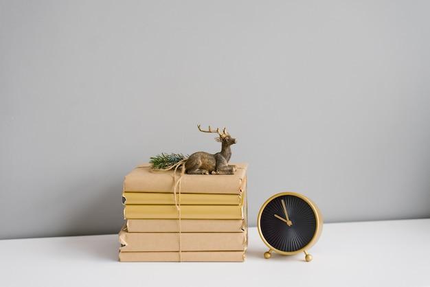 Pila di libri in copertine artigianali su una mensola bianca, souvenir cervi e orologio da tavolo