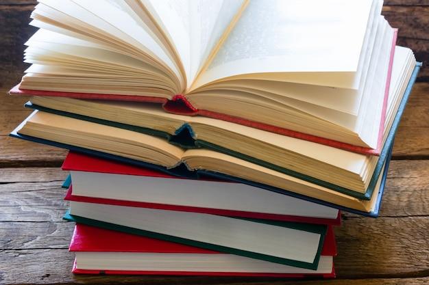 Pila di libri per l'apprendimento su un fondo di legno