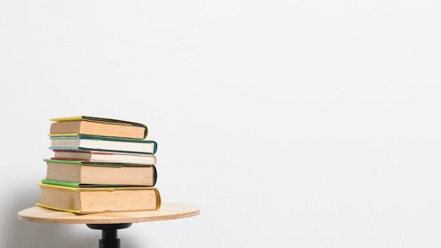 Pila di libri sulla tavola delle feci su fondo grigio
