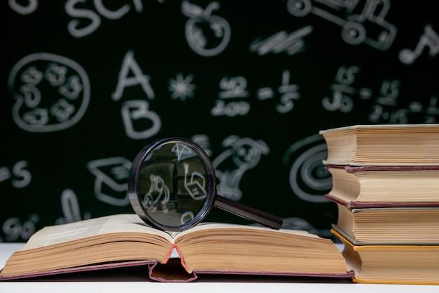 Pila di libro su un fondo verde della lavagna, di nuovo al concetto della scuola