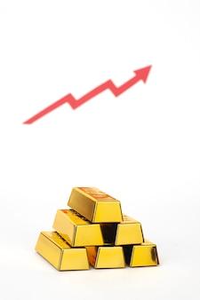 Pila di lingotti d'oro con freccia rossa su sfondo bianco