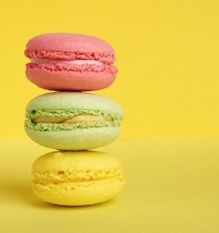 Pila di macarons al forno su uno sfondo giallo, delizioso dessert