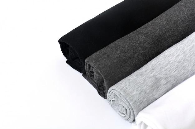 Pila di maglietta nera, grigia e bianca arrotolata su fondo bianco