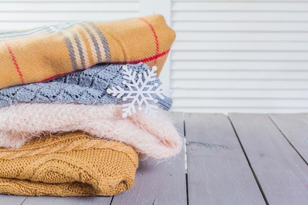 Pila di maglioni a maglia accoglienti bianchi su un tavolo di legno