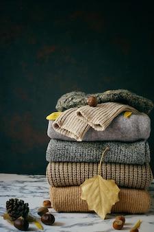Pila di maglioni a maglia accoglienti. concetto autunno-inverno, maglioni di lana lavorati a maglia. mucchio di abiti invernali a maglia, maglioni, maglieria