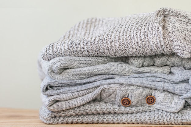 Pila di maglioni grigi accoglienti per autunno freddo sulla tavola di legno.