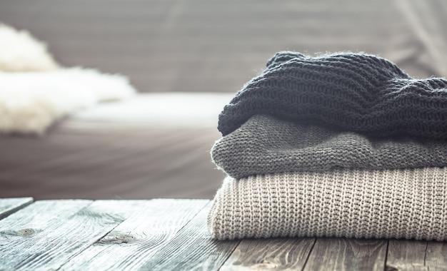 Pila di maglioni tricottati su una tavola di legno