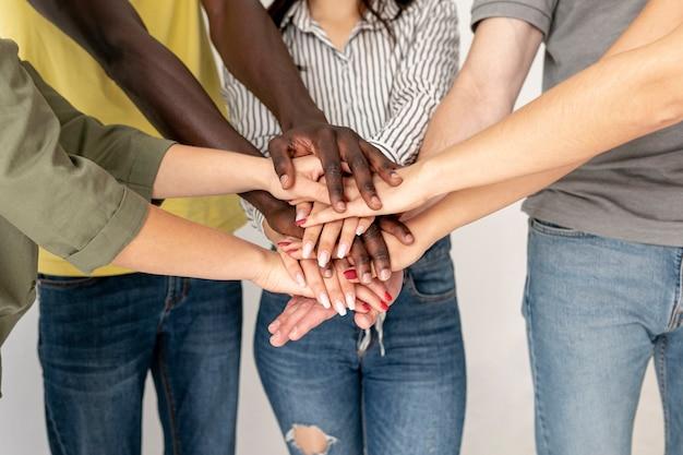 Pila di mani di giovani amici vista frontale