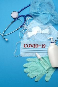 Pila di maschere mediche blu monouso con segno covid-19, guanti in lattice di gomma, occhiali, stetoscopio e alcool disinfettante per le mani antisettico su sfondo blu