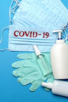 Pila di maschere per il viso mediche blu usa e getta con segno covid-19, guanti in lattice di gomma e disinfettante per le mani con alcool antisettico su sfondo blu