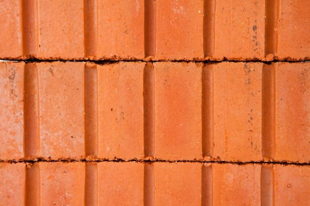 Pila di mattoni di argilla che costruiscono un muro