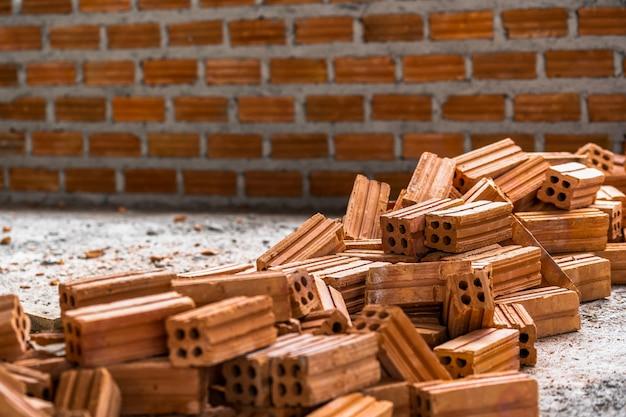 Pila di mattoni preparando per mansonry sopra la foto sfocato dello sfondo muro di mattoni,