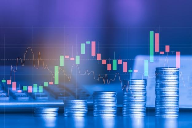Pila di moneta dei soldi con il grafico commerciale, concetto di investimento finanziario