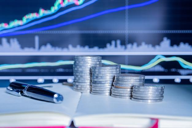 Pila di moneta dei soldi con il grafico commerciale.