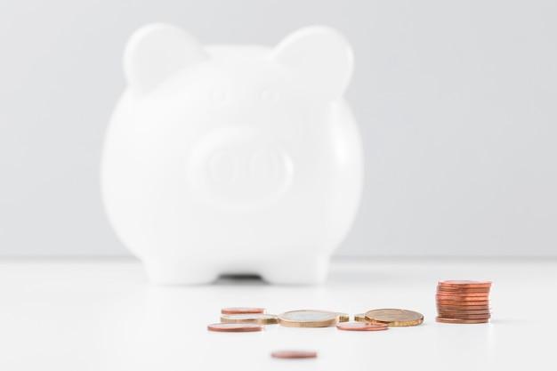 Pila di monete accanto al porcellino salvadanaio