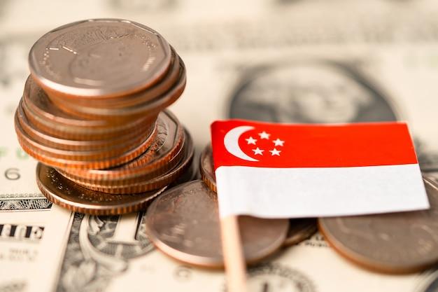 Pila di monete con la bandiera di singapore sulle banconote del dollaro di usa america.