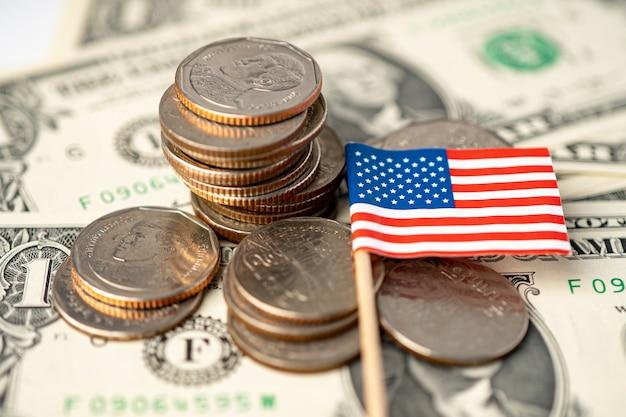 Pila di monete con la bandiera di usa america sulle banconote del dollaro.