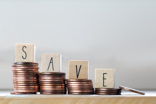 Pila di monete con la lettera di risparmi in blocco di legno, scale crescenti dei soldi di concetto di tempo di risparmio