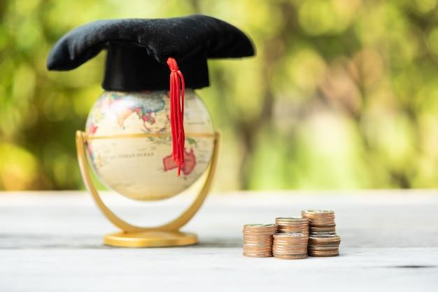Pila di monete davanti a un globo con cappello di laurea. finanza e istruzione.