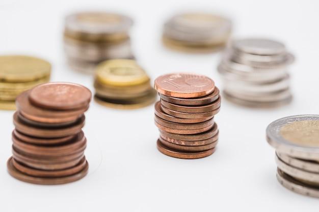 Pila di monete di rame con oro e argento su sfondo bianco