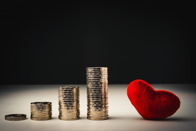 Pila di monete e cuore rosso