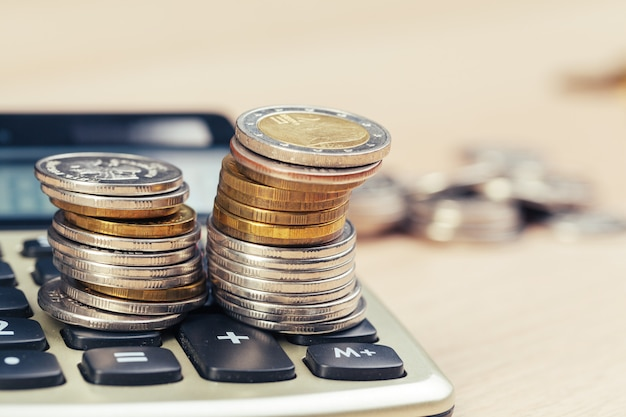 Pila di monete e di calcolatore, idea di concetto per finanza di affari