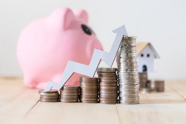 Pila di monete e salvadanaio, risparmio e concetto di investimento con crescente grafico in alto