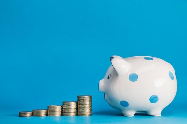 Pila di monete in aumento con porcellino salvadanaio in ceramica su sfondo bianco