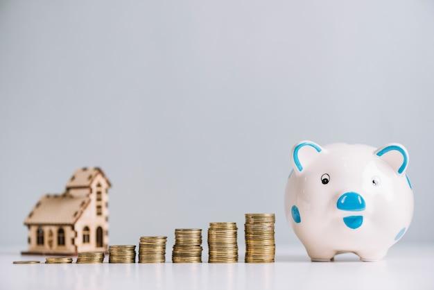 Pila di monete in aumento e salvadanaio davanti al modello di casa