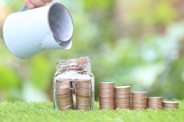 Pila di monete soldi e bottiglia di vetro