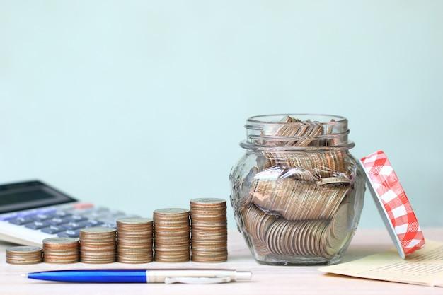 Pila di monete soldi e la bottiglia di vetro su sfondo bianco