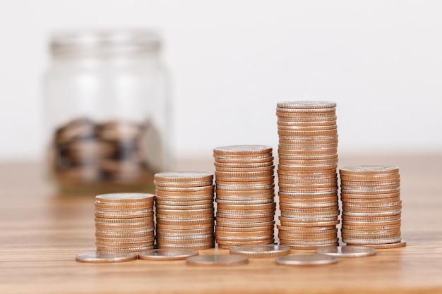 Pila di monete sullo scrittorio di legno per il concetto di risparmio dei soldi