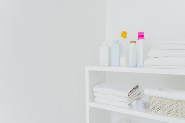 Pila di morbidi asciugamani bianchi con liquido per balsamo morbido