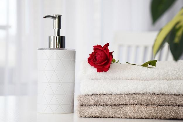 Pila di morbidi asciugamani di colore grigio e bianco con rosa rossa e contenitore di liquidi sullo sfondo. spa e benessere o concetto di salone di massaggi.