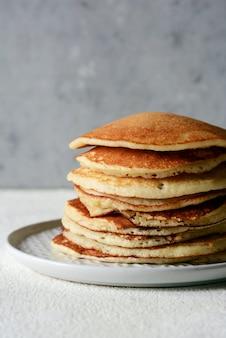 Pila di pancake casalinga dolce con miele per la prima colazione su un fondo grigio. dolce bella colazione. brunch. colazione in famiglia. concetto per caffè, ristoranti, fast food, bar