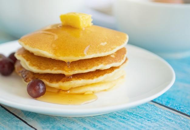 Pila di pancake casalinghi dolci con lo sciroppo di burro e la frutta per la prima colazione.