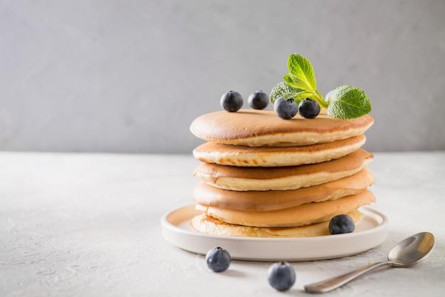 Pila di pancake con miele di versamento, mirtillo fresco e menta su luce
