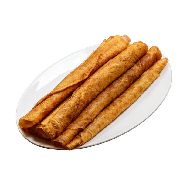 Pila di pancake deliziosi sul piatto isolato