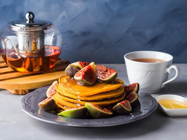 Pila di pancake di zucca con fichi e miele