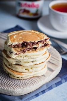 Pila di pancake farciti di nutella del cioccolato sul bordo di legno sulla tavola. concetto di colazione americana