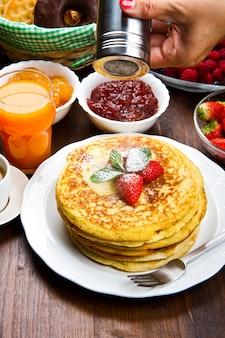 Pila di pancake tradizionali preparati al momento con fragole