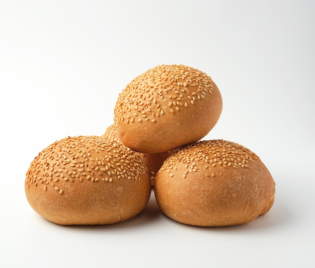 Pila di panino intero tondo al forno con semi di sesamo a base di farina di grano bianco