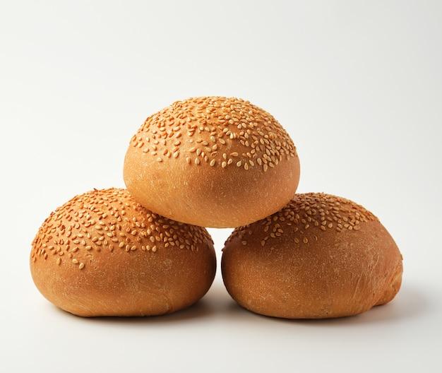 Pila di panino intero tondo al forno con semi di sesamo