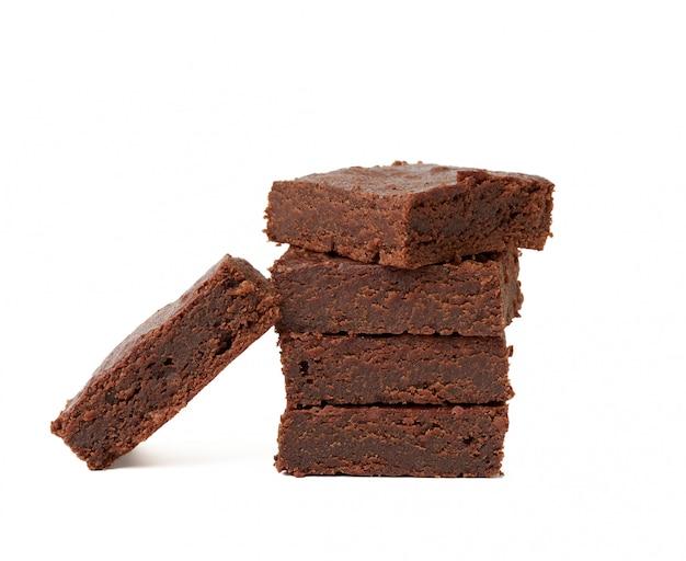 Pila di pezzi al forno quadrati di dolce di cioccolato del brownie isolato su un fondo bianco, dessert delizioso