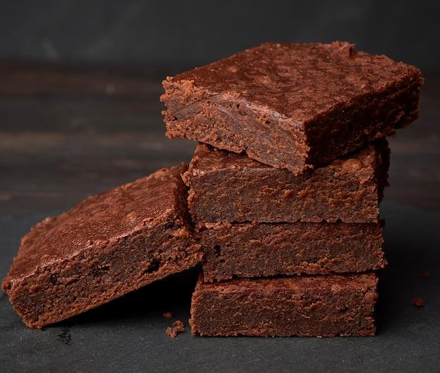 Pila di pezzi al forno quadrati di torta al cioccolato brownie